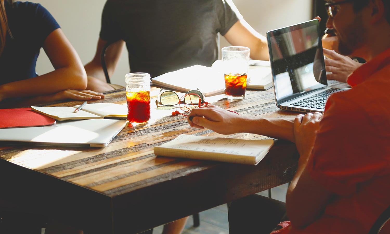Reunião de equipe criativa, cadernos e notebooks na mesa