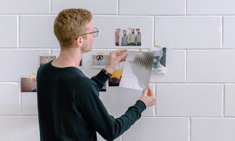 Pessoa colocando imagens em uma parede