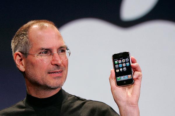 Steve Jobs segurando o primeiro modelo de iPhone